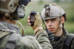 Soldiers holding navigator in hand and determines the location o Royalty Free Stock Photos