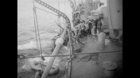 Soldiers jumping off  sinking warship into the sea, 1941 stock footage