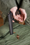 Soldiers load clip with cartridges into gun Colt Stock Image