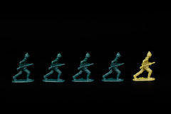 Soldiers Marching to different leader. A line of toy soldiers stood against a black background. They are marching in line with a soldier from the opposition Stock Image