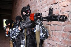 Soldiers in masks aiming the target with guns Stock Images