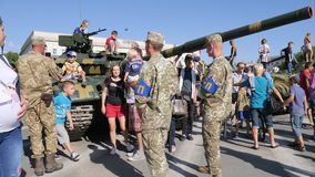 Soldiers into military uniform among urban children and adults near tank with large cannon on street in summer and. Kherson, Ukraine 24 August 2017: soldiers in stock video