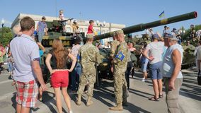 Soldiers into military uniform among urban people near tank with large cannon in center of city in summer. Kherson, Ukraine 24 August 2017: soldiers into stock video
