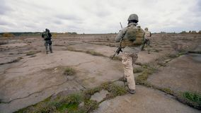 Soldiers with weapons are walking along the field stock video footage