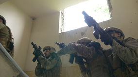 Soldiers on mission to kill terrorist leader ascending to first floor of an abandoned building in search of target. Soldiers on a mission to kill terrorist stock footage