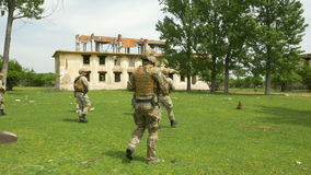 Soldiers on mission walking towards the objective in a rural area with abandoned ruin buildings stock video footage