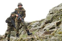 Soldiers moving on mountain with guns Stock Photo