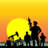 Soldiers with oil rigs on the background Stock Photo