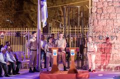 Soldiers - participants of the memorial ceremony stand during a siren near the half-masted flag in the Memorial Site To the Fallen. Nahariyya, Israel, April 17 stock photo