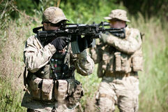 Soldiers on patrol aiming on enemy. U.S. soldiers during patrol on battle field, aiming on enemy Stock Photos