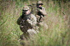 Soldiers on patrol hiding. U.S. soldiers during patrol on battle field, aiming on enemy, hidden in the grass Royalty Free Stock Photography