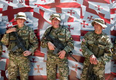 Soldiers posing. Georgian flag. Tbilisi. Georgia. TBILISI - MAY 26: The Independence Day of Georgia. Three soldiers posing in front of Georgian flag before Royalty Free Stock Images