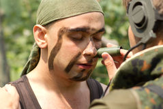 Soldiers putting on face paint Royalty Free Stock Photos