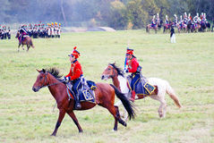 Soldiers-reenactors dressed in red ride horses. Royalty Free Stock Images