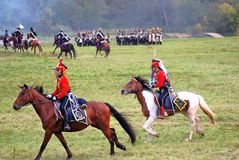Soldiers-reenactors dressed in red ride horses. Stock Photography