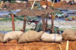 Soldiers-reenactors lay behind the barbed wire fence. Stock Photography