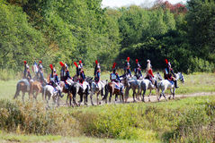 Soldiers-reenactors ride horses on the battle field. Royalty Free Stock Photography