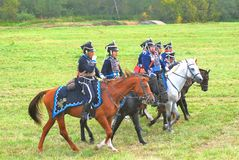 Soldiers-reenactors ride horses on the battle field. Royalty Free Stock Photos