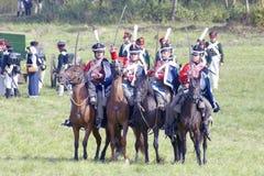 Soldiers-reenactors ride horses holding swords. Stock Photo
