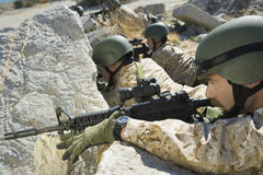 Soldiers With Rifles Hiding Behind Rocks Royalty Free Stock Images