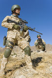 Soldiers With Rifles Patrolling Against Blue Sky Stock Images