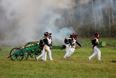 Soldiers run and carry a cannon Royalty Free Stock Image