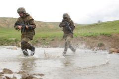 Soldiers running across the water Stock Image