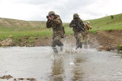 Soldiers running across the water Royalty Free Stock Photo