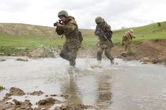 Soldiers running across the water Royalty Free Stock Photography