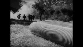 Soldiers running into large tubes during combat training stock footage