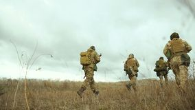 Soldiers running over field. Soldiers running through dry field. Soldiers running over field. Scout group performs a military mission. Group of soldiers running stock footage