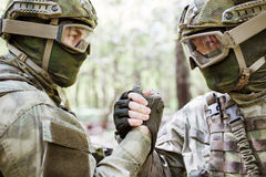 Soldiers shaking hands in woods stock photography
