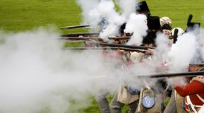 Soldiers shooting. English red coat soldiers, anno 1807, shooting with black powder Royalty Free Stock Image