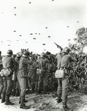 Soldiers shooting at enemy parachuting into field Royalty Free Stock Photo