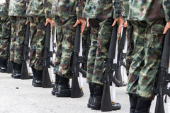 Soldiers stand holding a gun. Royalty Free Stock Images