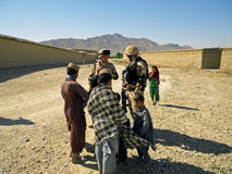 Soldiers talking to some kids in Afghanistan Royalty Free Stock Photos