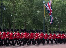 Soldiers in traditional uniform marching down The Mall in London during the Trooping the Colour ceremony. Marching soldiers with rifles walking down The Mall in Royalty Free Stock Photo