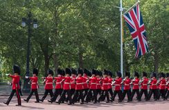 Soldiers in traditional uniform marching down The Mall in London during the Trooping the Colour ceremony. Marching soldiers with rifles on their shoulders Stock Image
