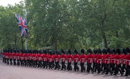 Soldiers in traditional uniform marching down The Mall in London during the Trooping the Colour ceremony. Marching soldiers with rifles on their shoulders Royalty Free Stock Photos