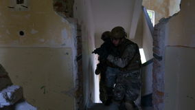 Soldiers unit entering into the ruined building checking their military objective stock footage