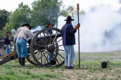 Soldiers using  a cannon. Union soldiers are shrouded on a smokey hilltop after firing off an old cannon Royalty Free Stock Image