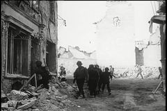 Soldiers walking through bombed out building