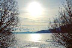 Sole che riflette sul lago innevato ghiacciato immagini stock
