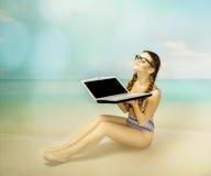 Sole della presa della ragazza del nerd sulla spiaggia immagini stock