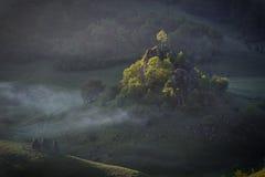 Sole di mattina con nebbia sopra un paesaggio della montagna con le rocce e gli alberi alla luce solare diretta Fundatura Ponorul Immagini Stock