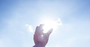 Sole di raccolto della mano a cielo blu ed alla nuvola Fotografia Stock Libera da Diritti