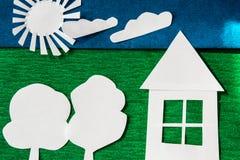 Sole e casa di carta su backgound verde e blu immagine stock libera da diritti