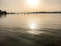 Sole e luce di sera sopra il lago con le riflessioni e le ondulazioni pacifiche in lago Murten/Morat in Svizzera Immagine Stock