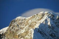 Sole e nuvole sul picco della neve dell'alta montagna Fotografie Stock Libere da Diritti