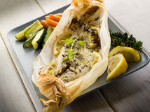 Sole fish cocked in a wrapper. With herbs and sliced lemon Royalty Free Stock Photo